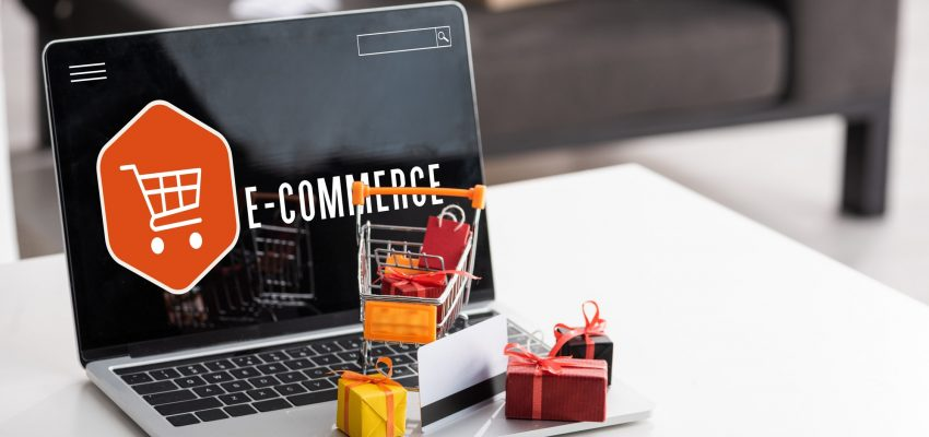 Toy gift boxes and credit card on laptop with e-commerce lettering on table